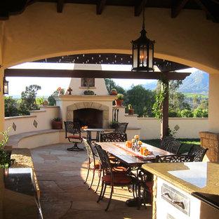 Immagine di un patio o portico mediterraneo di medie dimensioni e dietro casa con pavimentazioni in pietra naturale, un gazebo o capanno e un caminetto