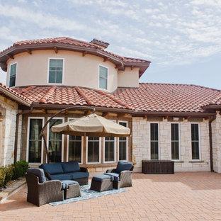 Immagine di un ampio patio o portico stile rurale in cortile con un focolare, pavimentazioni in pietra naturale e un tetto a sbalzo