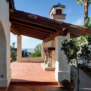 This is an example of a large mediterranean back patio in San Diego with an outdoor kitchen, tiled flooring and no cover.