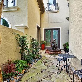 Esempio di un ampio patio o portico mediterraneo in cortile con fontane e pavimentazioni in pietra naturale