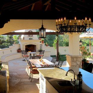 Foto di un patio o portico mediterraneo di medie dimensioni e dietro casa con pavimentazioni in pietra naturale, un gazebo o capanno e un caminetto
