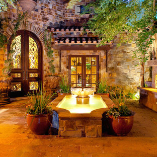 Photo of an expansive country courtyard patio in Phoenix with a water feature, natural stone pavers and no cover.