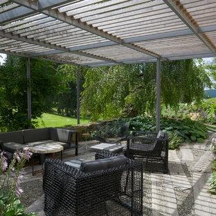 Foto di un grande patio o portico contemporaneo dietro casa con una pergola, fontane e ghiaia