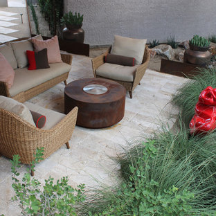 Small modern back patio in Phoenix with natural stone paving and an awning.