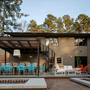 Photo of a midcentury backyard patio in Raleigh with a pergola and decking.