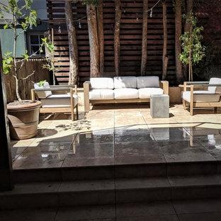 Idee per un grande patio o portico etnico dietro casa con piastrelle e nessuna copertura