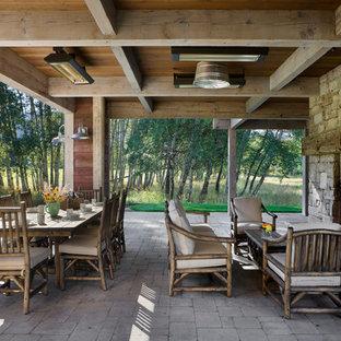 Exemple d'une terrasse nature avec un foyer extérieur et une extension de toiture.