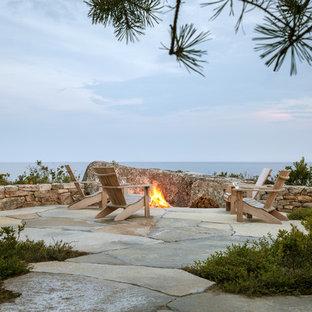 Idee per un ampio patio o portico minimal dietro casa con un focolare, pavimentazioni in pietra naturale e nessuna copertura