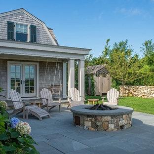 Foto di un patio o portico country di medie dimensioni e dietro casa con un focolare, pavimentazioni in cemento e un tetto a sbalzo