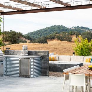 Esempio di un patio o portico country dietro casa con lastre di cemento e una pergola