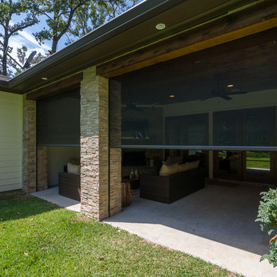 Inspiration for a mid-sized contemporary backyard concrete patio kitchen remodel in New Orleans with a roof extension