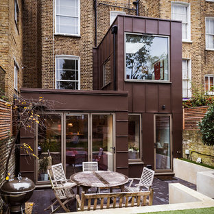Medium sized contemporary back patio in London with concrete slabs and no cover.