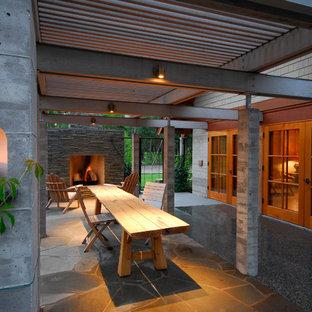 Idee per un ampio patio o portico minimalista dietro casa con un focolare, una pergola e graniglia di granito