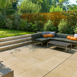 Design ideas for a medium sized contemporary back patio in London with natural stone paving and no cover.