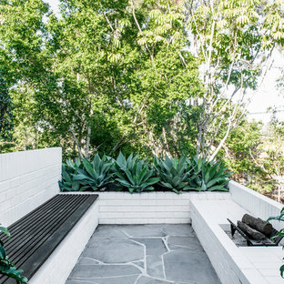 Design ideas for a mid-sized midcentury patio in Brisbane.