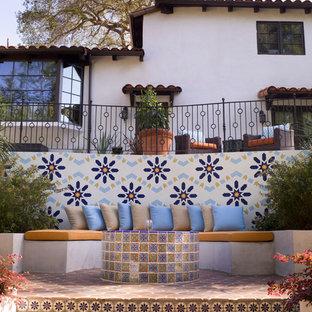 Ispirazione per un patio o portico mediterraneo con piastrelle e nessuna copertura