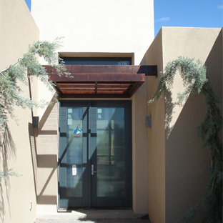 This is an example of a modern courtyard patio in Albuquerque with brick paving and an awning.
