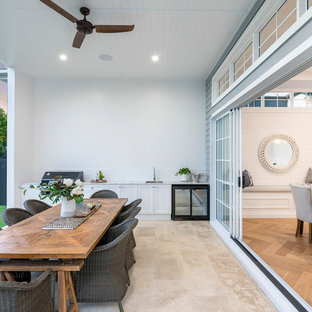 Transitional backyard patio in Brisbane with an outdoor kitchen, tile and a roof extension.