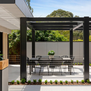This is an example of a mid-sized contemporary backyard patio in Melbourne with tile and a pergola.