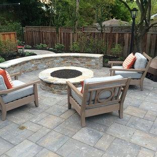 Ispirazione per un patio o portico classico di medie dimensioni e dietro casa con un focolare, cemento stampato e nessuna copertura