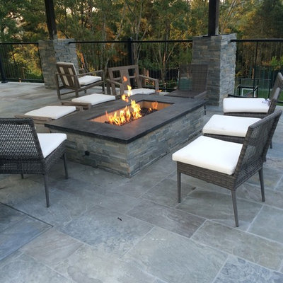 Large trendy backyard stamped concrete patio photo in Other with a fire pit and a roof extension
