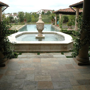 Design ideas for an expansive mediterranean courtyard patio in Toronto with a water feature, natural stone pavers and no cover.