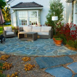 Immagine di un ampio patio o portico dietro casa con un focolare, pavimentazioni in pietra naturale e nessuna copertura