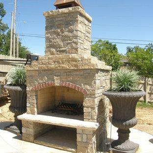 Esempio di un patio o portico classico dietro casa con un caminetto, lastre di cemento e nessuna copertura