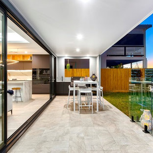 Photo of a contemporary backyard patio in Brisbane with an outdoor kitchen, tile and a roof extension.