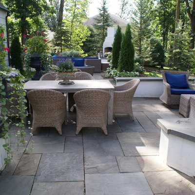 Example of a large classic backyard stone patio design in Minneapolis with no cover