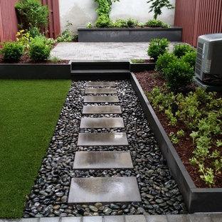 Ispirazione per un piccolo patio o portico design dietro casa con un giardino in vaso, pavimentazioni in pietra naturale e nessuna copertura