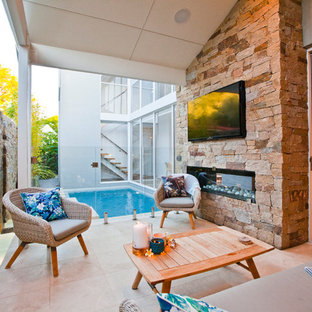 Design ideas for a small beach style backyard patio in Perth with tile and a roof extension.