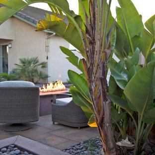 Idee per un piccolo patio o portico tropicale dietro casa con un focolare e pavimentazioni in cemento
