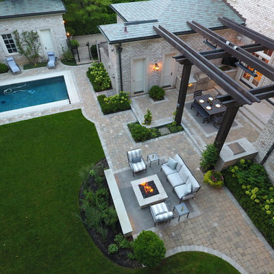 Inspiration for a large timeless backyard stone patio kitchen remodel in Chicago with a pergola