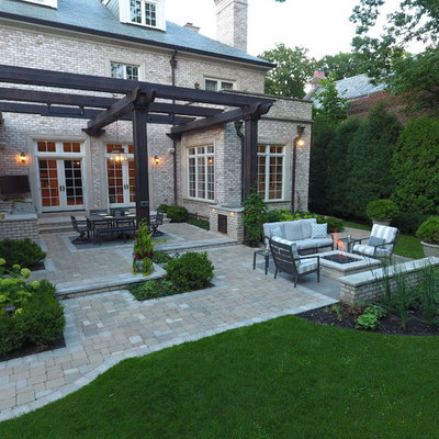 Patio kitchen - large traditional backyard stone patio kitchen idea in Chicago with a pergola