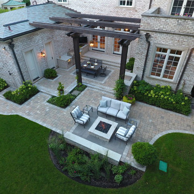 Example of a large classic backyard stone patio kitchen design in Chicago with a pergola