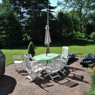 Ispirazione per un patio o portico stile marinaro di medie dimensioni e dietro casa con pavimentazioni in mattoni