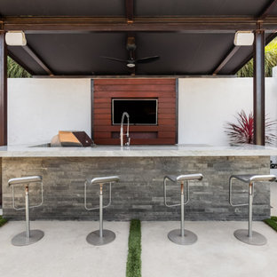 This is an example of a large modern back patio in Los Angeles with an outdoor kitchen, an awning and concrete paving.