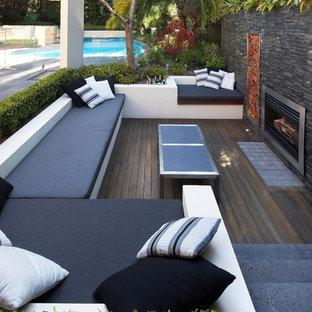 Inspiration pour une terrasse arrière design avec un foyer extérieur.