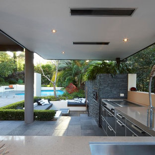 Ejemplo de patio actual, de tamaño medio, en patio trasero y anexo de casas, con cocina exterior