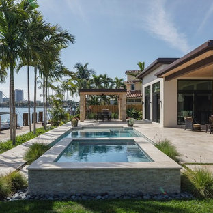 Patio - contemporary patio idea in Miami with a roof extension