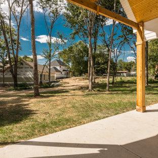 Esempio di un patio o portico country di medie dimensioni e dietro casa con un caminetto, lastre di cemento e un tetto a sbalzo