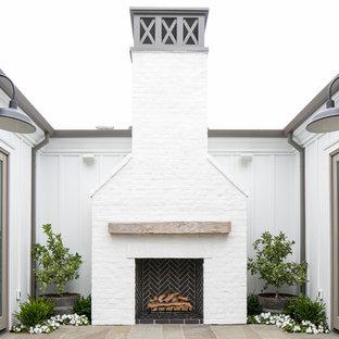 Foto di un patio o portico country di medie dimensioni e dietro casa con un focolare, piastrelle e nessuna copertura