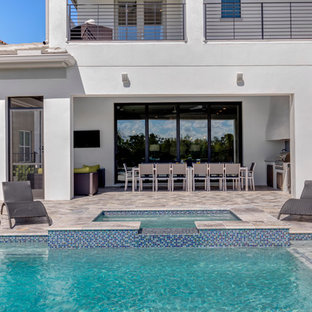 Ispirazione per un grande patio o portico moderno dietro casa con piastrelle e un tetto a sbalzo