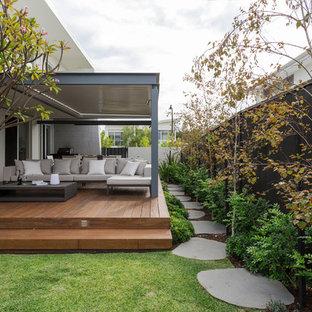 Ejemplo de patio actual, de tamaño medio, con entablado y pérgola