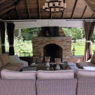 Ispirazione per un patio o portico classico di medie dimensioni e dietro casa con un focolare, pavimentazioni in cemento e un gazebo o capanno