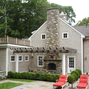 他の地域の広いトラディショナルスタイルのおしゃれな裏庭のテラス (ファイヤーピット、天然石敷き、パーゴラ) の写真