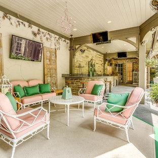 Immagine di un ampio patio o portico shabby-chic style dietro casa con pavimentazioni in pietra naturale e un tetto a sbalzo