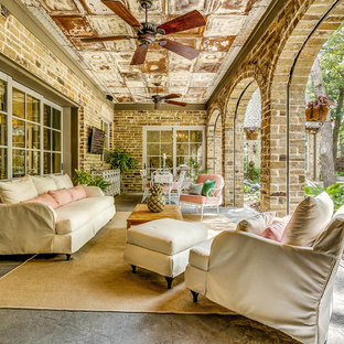 Design ideas for an expansive romantic back patio in Dallas with an outdoor kitchen, natural stone paving and a roof extension.