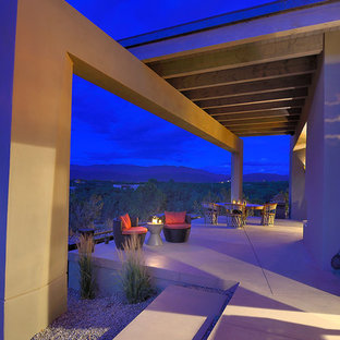 Photo of a large modern backyard patio in Albuquerque with concrete slab and a pergola.